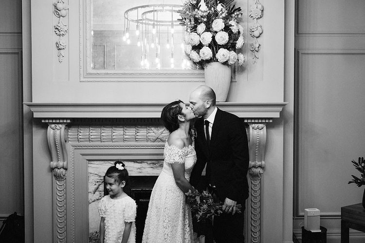 Bride in Lace Whistles Wedding Dress with High/Low Hem and Bardot Neckline | Groom in Black Reiss Jacket and Black Nudie Jeans with Church's Shoes | Flower Girl in White Zara Dress with Short Sleeves and Scoop Back | Wedding Ceremony at Old Marylebone Town Hall | High Street Wedding Dress for an Intimate Crouch End Pub Wedding with Bright Flowers | Miss Gen Photography