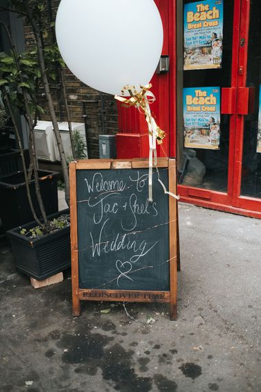 Chalkboard Welcome Sign | Oversized White Balloon with Gold Ribbon | Victoria Stakes Pub Wedding Reception | High Street Wedding Dress for an Intimate Crouch End Pub Wedding with Bright Flowers | Miss Gen Photography