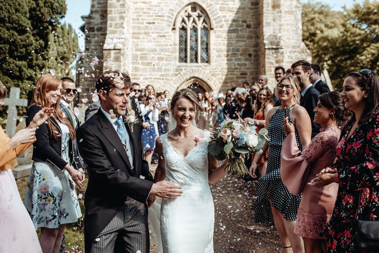 Church Confetti Moment | Bride in Lace Pronovias Wedding Dress | Groom in Traditional Morning Suit by Macinnes Bespoke Tailoring | Classic Country Wedding at Wadhurst Castle, East Sussex with Wedding Suppliers from RMW. The List | Foto Memories Photography
