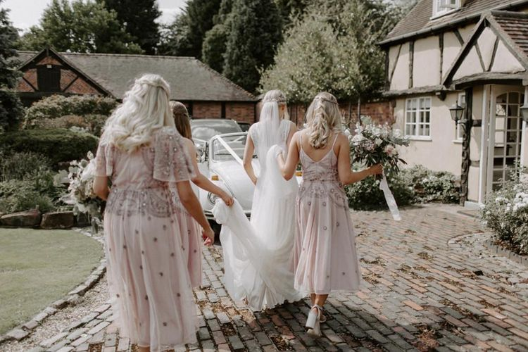 Bride in Charlie Brear Carenne Wedding Dress with Corette Lace Overdress  and Bridesmaids in Pink Embellished ASOS Dresses