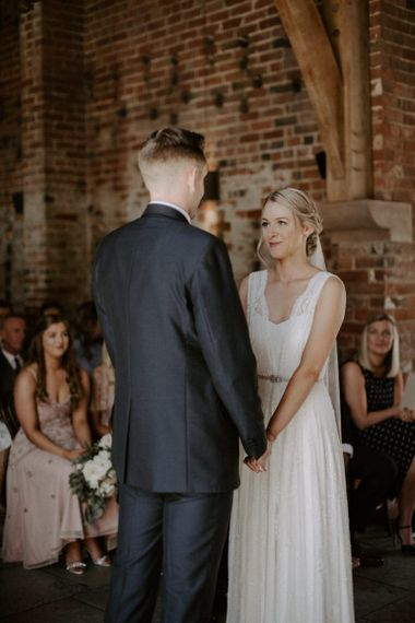 Bride in Charlie Brear Carenne Wedding Dress with Corette Lace Overdress and Groom in Navy Peter Posh Suit with Wool Waistcoat Exchanging Vows