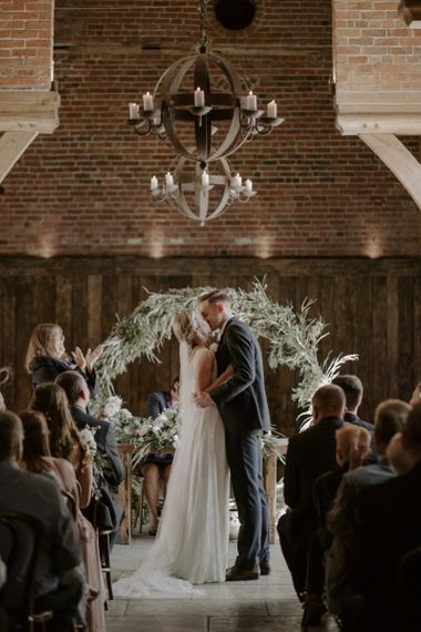 Bride in Charlie Brear Carenne Wedding Dress with Corette Lace Overdress and Groom in Navy Peter Posh Suit with Wool Waistcoat Kissing in Front of Greenery Moon Gate