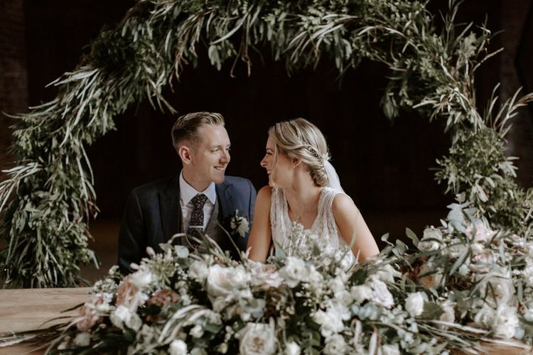 Bride and Groom Signing The Register in Front of a Greenery Moon Gate