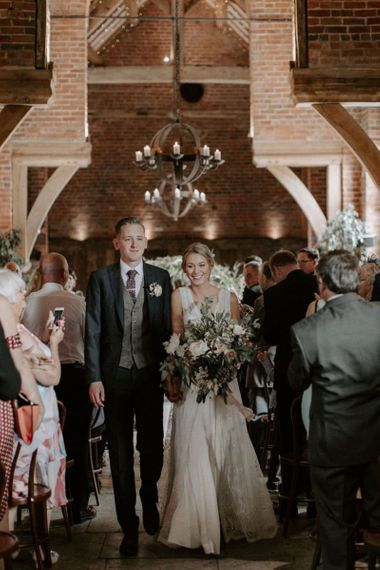 Bride in Charlie Brear Carenne Wedding Dress with Corette Lace Overdress and Groom in Navy Peter Posh Suit Walking Up The Aisle as Husband & Wife