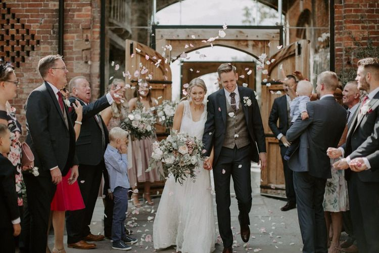 Confetti Moment with Bride in Charlie Brear Carenne Wedding Dress with Corette Lace Overdress and Groom in Navy Peter Posh Suit