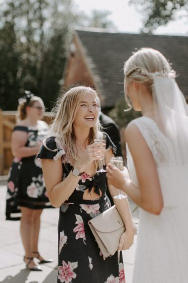 Bride in Charlie Brear Carenne Wedding Dress with Corette Lace Overdress Talking to a Wedding Guest
