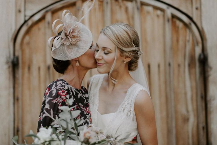 Mother of The Bride Kissing Her Daughter in a  Charlie Brear Carenne Wedding Dress with Corette Lace Overdress