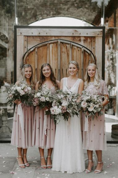 Bridal Party Portrait with Bride in a  Charlie Brear Carenne Wedding Dress with Corette Lace Overdress and Bridesmaids in Pink Embellished Dresses