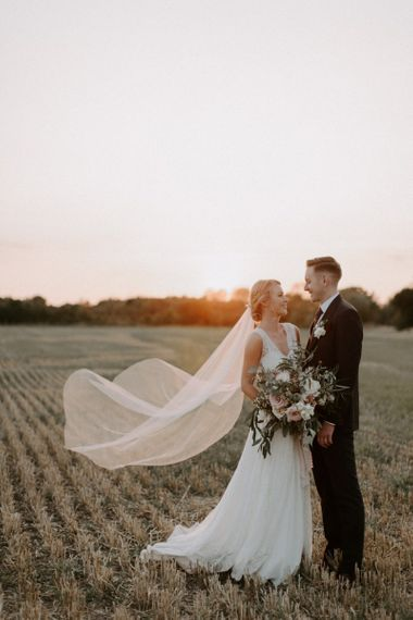 Golden Hour Portrait with Bride in Charlie Brear Carenne Wedding Dress with Corette Lace Overdress and Groom in Navy Peter Posh Suit