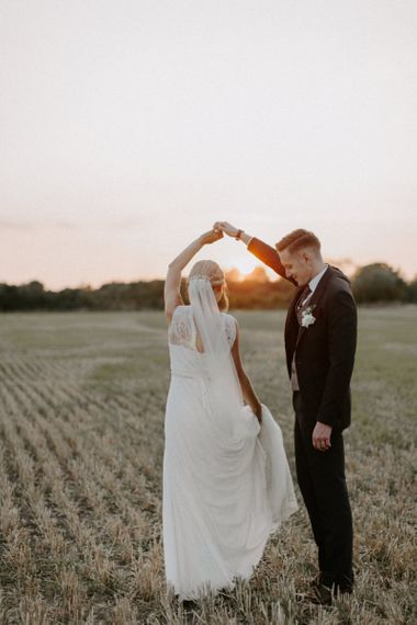Sunset Portrait with Bride in Charlie Brear Carenne Wedding Dress with Corette Lace Overdress and Groom in Navy Peter Posh Suit