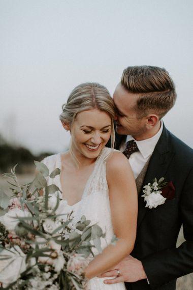 Groom in Navy Peter Posh Suit Kissing His Bride
