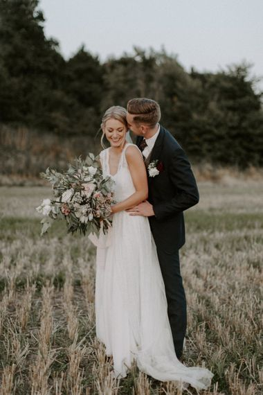 Groom in Navy Peter Posh Suit Kissing His Bride in Charlie Brear Carenne Wedding Dress with Corette Lace Overdress