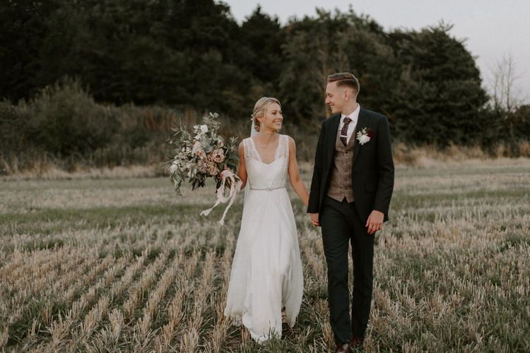 Bride in Charlie Brear Carenne Wedding Dress with Corette Lace Overdress and Groom in Navy Peter Posh Suit Walking Through a Field