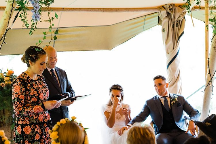 Wedding Ceremony Emotions | Bride in Laced KatyaKatya Wedding Dress with Cap Sleeves and Ribbon Belt | Groom in Blue T.M Lewin Suit with Navy Hawkes Bespoke Outfitters Waistcoat | Lace KatyaKatya Dress for Tipi Wedding at Fforest Farm | Claudia Rose Carter Photography