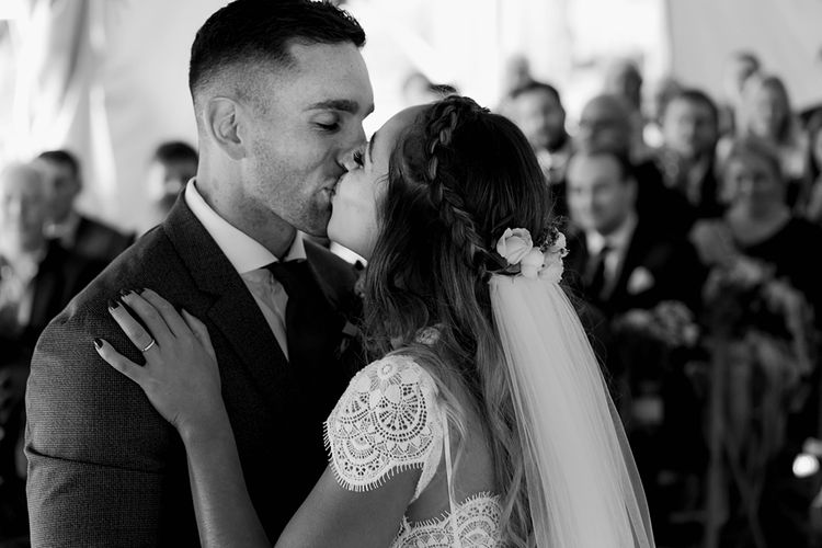 Wedding Ceremony | First Kiss | Bride in Laced KatyaKatya Wedding Dress with Cap Sleeves and Ribbon Belt | Groom in Blue T.M Lewin Suit with Navy Hawkes Bespoke Outfitters Waistcoat | Lace KatyaKatya Dress for Tipi Wedding at Fforest Farm | Claudia Rose Carter Photography