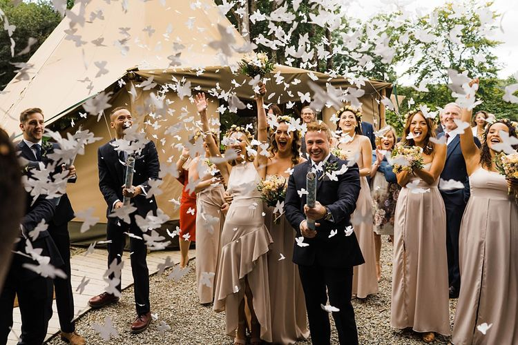 Confetti Cannon | Bridesmaids in Dusty Pink ASOS Dresses | Flower Crowns | Groomsmen in Navy Moss Bros. Suits | Lace KatyaKatya Dress for Tipi Wedding at Fforest Farm | Claudia Rose Carter Photography