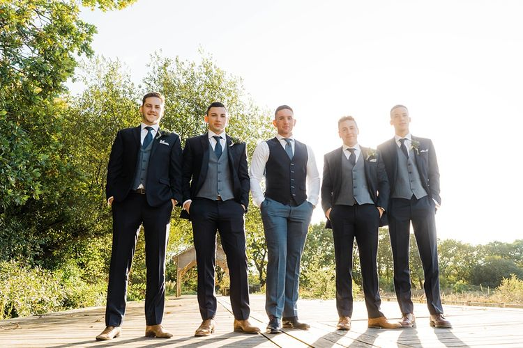 Groom in Blue T.M Lewin Suit with Navy Hawkes Bespoke Outfitters Waistcoat | Groomsmen in Navy Moss Bros. Suits | Lace KatyaKatya Dress for Tipi Wedding at Fforest Farm | Claudia Rose Carter Photography