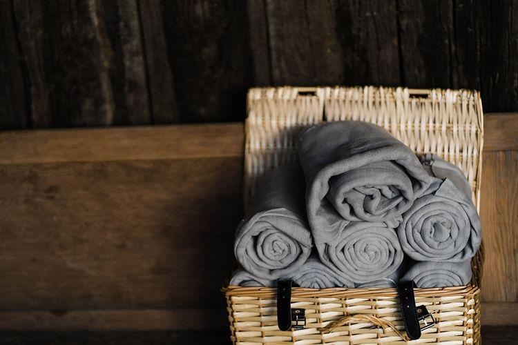 Wedding Reception Decor | Grey Blankets in Wicker Basket | Lace KatyaKatya Dress for Tipi Wedding at Fforest Farm | Claudia Rose Carter Photography