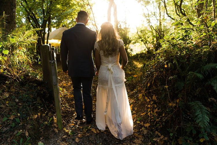 Bride in Laced KatyaKatya Wedding Dress with Cap Sleeves and Ribbon Belt | Groom in Blue T.M Lewin Suit with Navy Hawkes Bespoke Outfitters Waistcoat | Lace KatyaKatya Dress for Tipi Wedding at Fforest Farm | Claudia Rose Carter Photography