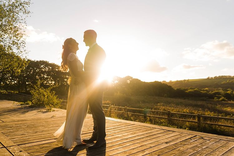 Bride in Laced KatyaKatya Wedding Dress with Cap Sleeves and Ribbon Belt | Red Christian Louboutin Shoes | Groom in Blue T.M Lewin Suit with Navy Hawkes Bespoke Outfitters Waistcoat | Lace KatyaKatya Dress for Tipi Wedding at Fforest Farm | Claudia Rose Carter Photography
