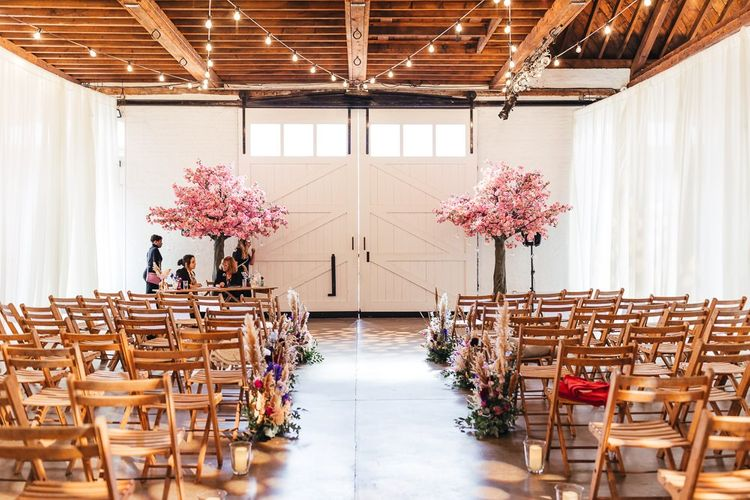 Pink blossom trees and vibrant florals at dry hire wedding venue