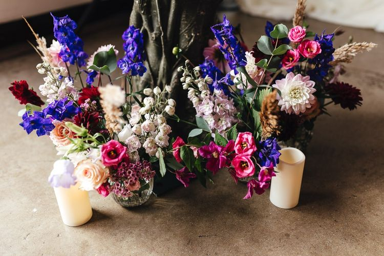 Vibrant floral and candle decor at industrial dry hire wedding venue