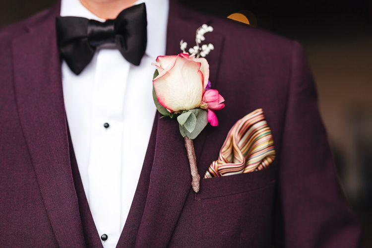 Groom wearing purple three piece suit with pink rose buttonhole