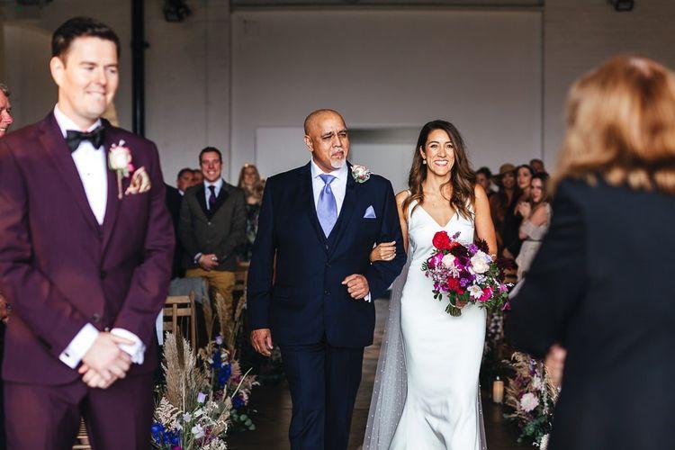 Bride walking down the aisle wearing polka dot Watteau train