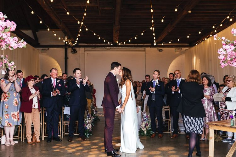Industrial ceremony with festoon lighting and pink blossom trees