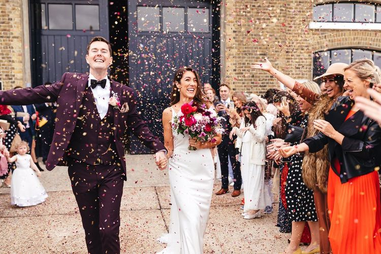 Bride clutching vibrant bouquet and groom wearing three piece suit