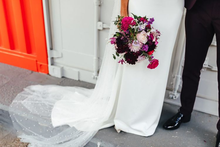 Brides beautiful polka dot embellished Watteau train and vibrant floral bouquet