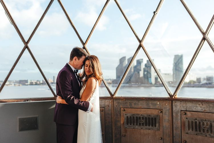 Bride and groom embrace at London celebration wearing three piece suit and beautiful dress with polka dot train