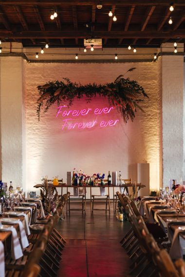 Pink personalised neon sign and foliage decor at dry hire wedding venue