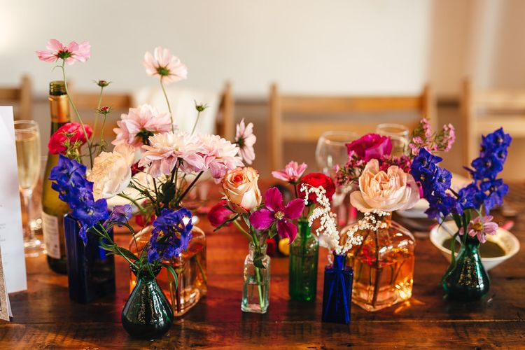 Vibrant floral table arrangements in colourful glass vases at industrial reception in London