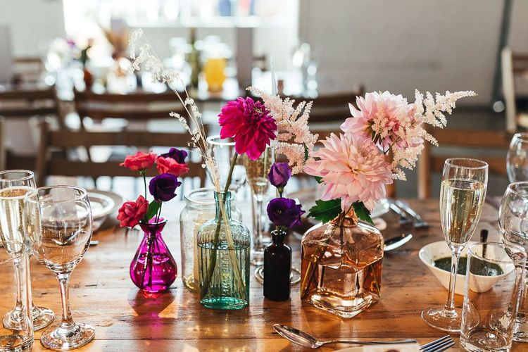 Vibrant floral table arrangements displayed in colourful glass vases