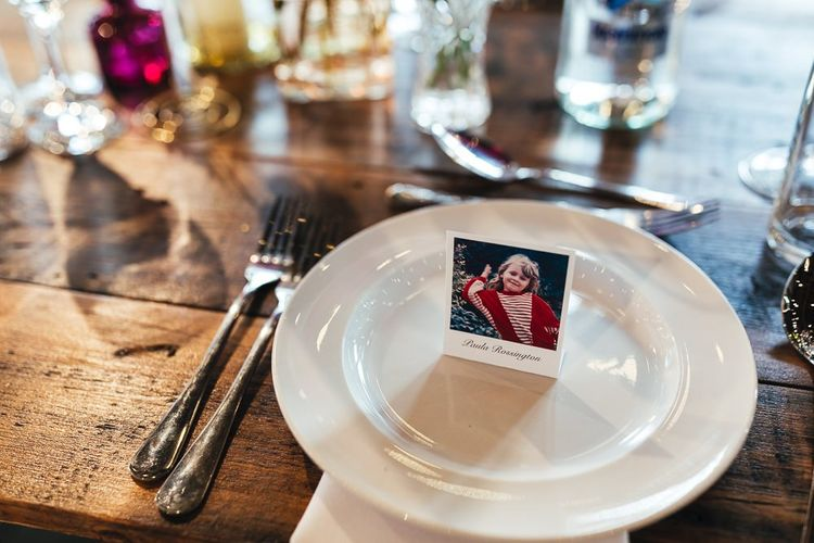 Polaroid style place name settings with colourful glass vase table centrepieces