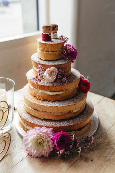 Five tier cake with pink floral decorations at industrial styled reception in London