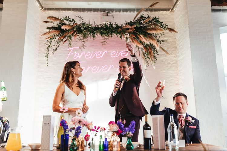 Raise a glass at industrial style reception with personalised neon sign