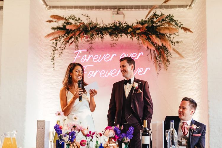 Pink neon sign and vibrant florals at dry hire wedding venue