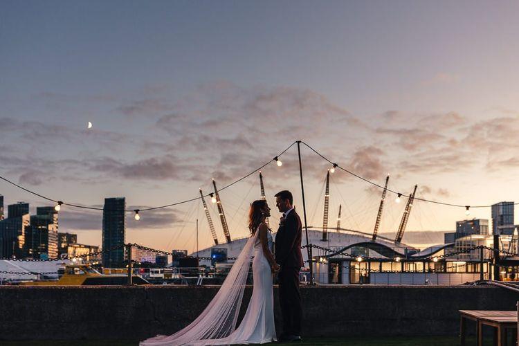 Sunset views across London with bride wearing beautiful Watteau train