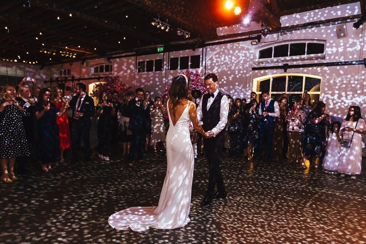 Bride and grooms first dance with glitter ball and pink blossom trees