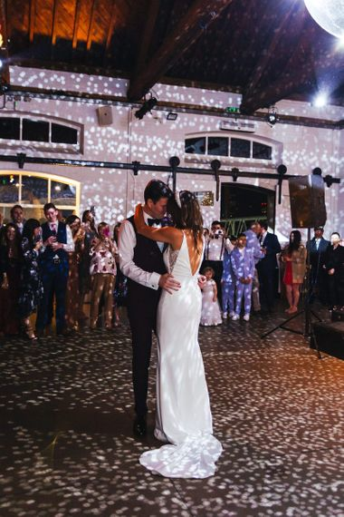 Bride and grooms first dance at industrial reception with glitter ball