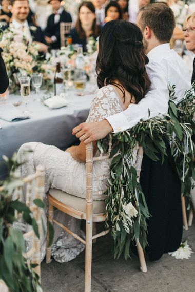 Bride and Groom During Wedding Breakfast | Top Table | Foliage Decoration for Chairs | Bride in Hermione de Paula Wedding Gown with Short Sleeves and Personalised Embroidery | Stunning Syon Park Wedding with Quill Stationery Suite | Nancy Ebert Photography