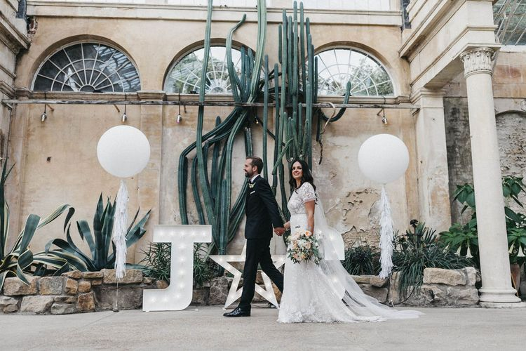 The Cactus House at Syon Park | Giant White Balloons | Giant Letter Lights | Bride in Hermione de Paula Wedding Gown with Short Sleeves and Personalised Embroidery | Cathedral Veil | Groom in Navy Lanvin Tuxedo and Black Burberry Shoes | Burgundy Bow Tie | Blush, Cream and Pink Bridal Bouquet | Stunning Syon Park Wedding with Quill Stationery Suite | Nancy Ebert Photography