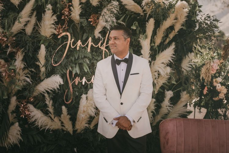 Groom in White Dinner Jacket Standing at the Greenery and Pampas Grass Altar