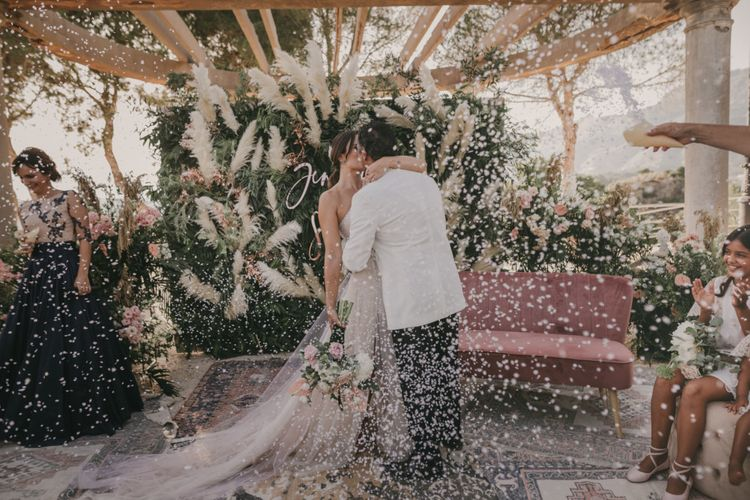 Bride and Groom Kissing During the Confetti Moment at the Altar