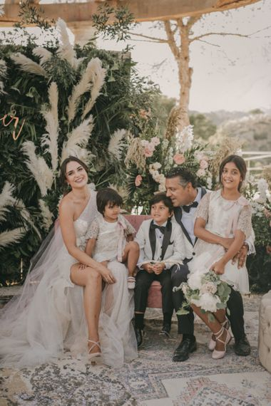 Stylish Bride and Groom Sitting with Their Children