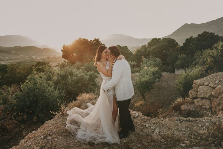 Bride in One Shoulder Muse by Berta Wedding Dress and Groom in White Dinner Jacket Standing on a Spanish Mountain