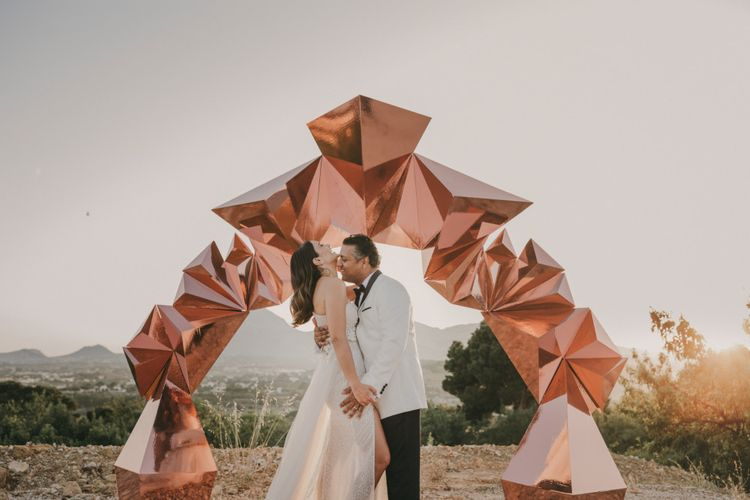 Bride in One Shoulder Muse by Berta Wedding Dress and Groom in White Dinner Jacket Standing in Front of a Copper Geometric Structure