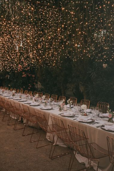 Outdoor Wedding Reception with Fairy Lights Canopy & Rose Gold Wire Chairs